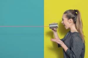 Jeune femme devant un mur jaune et bleu en train de crier dans une boite de conserve reliée à un fil rouge