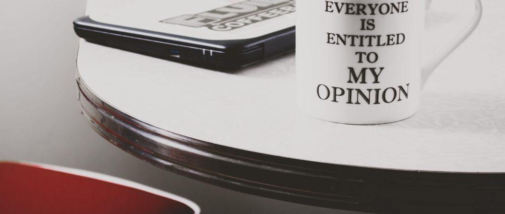 Tasse blanche avec inscription posée sur un bureau avec ordinateur
