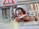 homme avec casque anti bruit près d'une machine industrielle qui tient et regarde une pièce