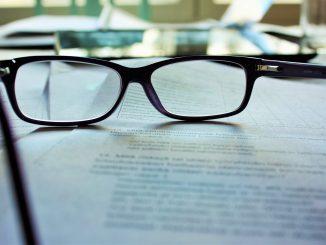 des lunettes posées sur un contrat