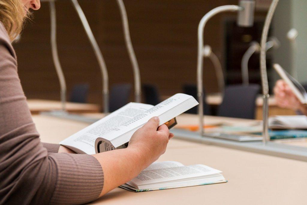 personne qui lit un livre à la bibliothèque