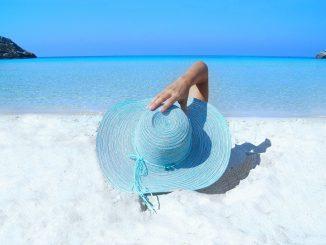 personne allongée sur une plage qui tient son chapeau bleu sur sa tête