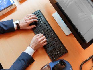 personne en costume qui tape sur un clavier d'ordinateur de bureau