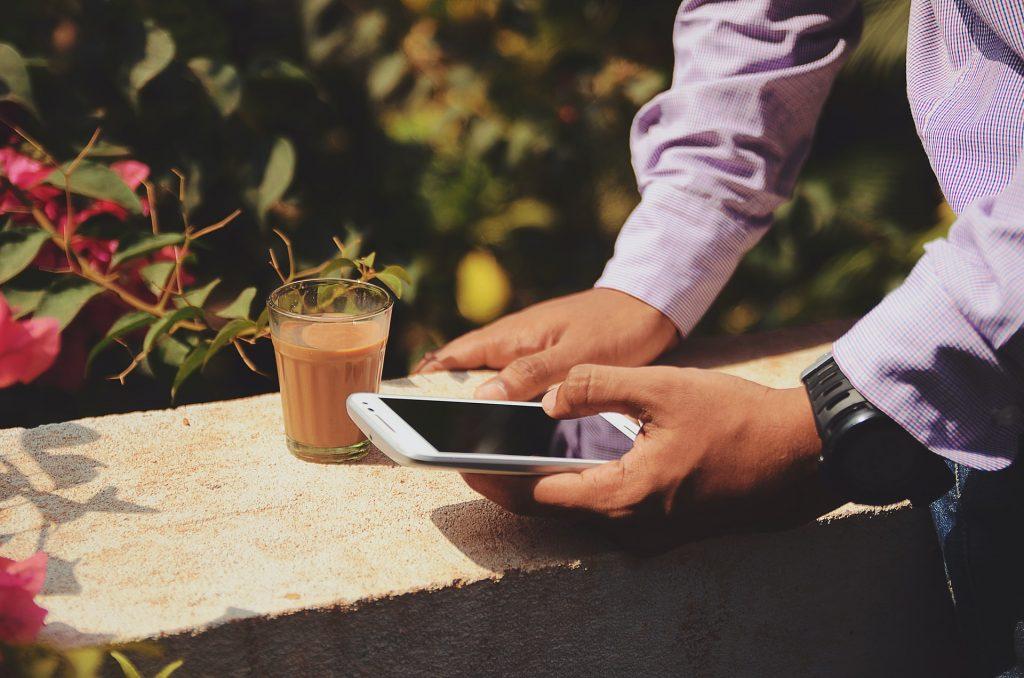 Wi-fi hôtel, homme sur son téléphone portable avec un café
